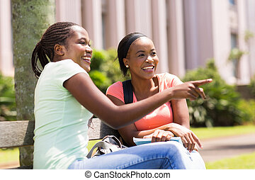 young african college students sitting outdoors
