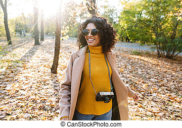 Beautiful young african happy woman walking outdoors in a spring park.