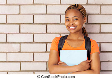 young african university girl standing against the wall