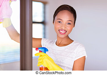young african woman cleaning window glass
