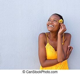 Beautiful young african woman holding a flower