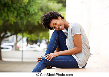 Beautiful young african woman sitting by a city street