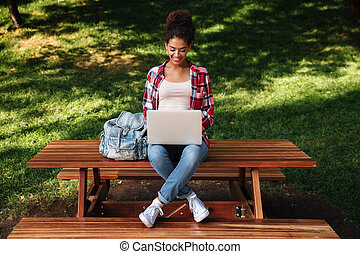 Beautiful young african woman sitting outdoors