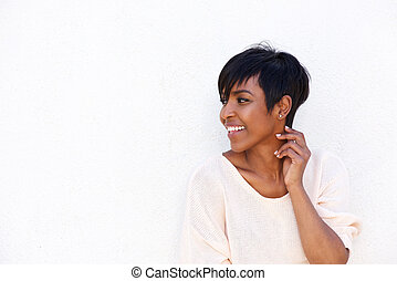 Beautiful young african woman smiling by white background