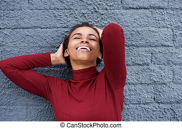 beautiful young african woman smiling with hand in hair