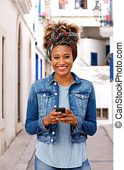 Beautiful young african woman standing outdoors with smart phone