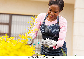 young african woman trimming plants