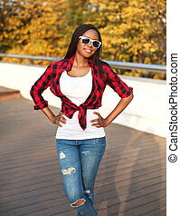 Beautiful young african woman wearing a sunglasses and red checkered shirt in city