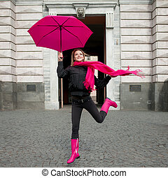 Beautiful young and happy blond woman with colorful umbrella...