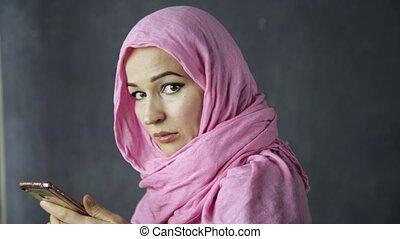 beautiful young arabian muslim woman in pink hijab talking...