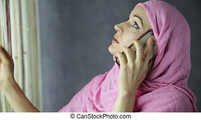 beautiful young arabian woman standing by a window and talking on cell phone
