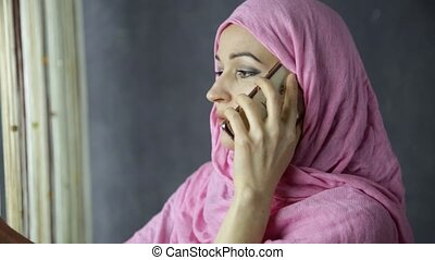 beautiful young arabian woman standing by a window and...