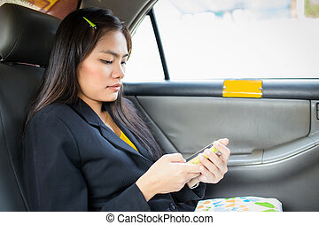 Beautiful young Asian businesswomen using a smart phone on car
