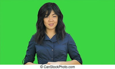 Beautiful young asian woman doing a presentation on a Green Screen, Chroma Key