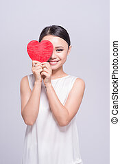 Beautiful young asian woman holding red heart on white