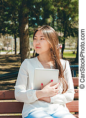 Beautiful young asian woman holding tablet computer