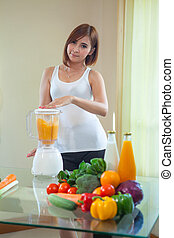 Beautiful Young Asian Woman Making Fruit Smoothie in Blender