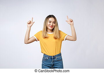 Beautiful young Asian woman pointing her finger up with cheerful expression, on white background.