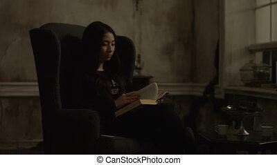 Beautiful young asian woman reading book at night