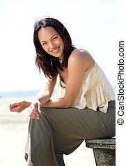 Beautiful young asian woman smiling outdoors