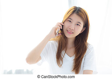 Beautiful young asian woman smiling sitting and relax on the bed in the morning, girl using mobile smart phone talking enjoy at bedroom, communication concept.