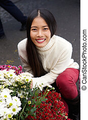 Beautiful young asian woman smiling with flowers at shop