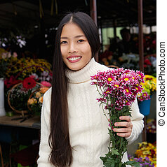 Beautiful young asian woman smiling with flowers