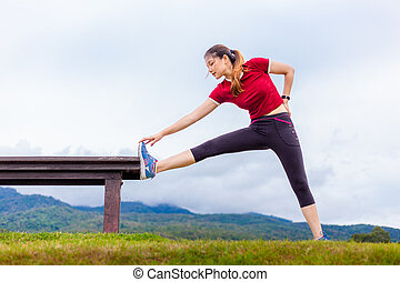 Beautiful young Asian woman stretching during her morning exercise at a park on a cloudy sky day, with mouintains and sky background, healthy lifestyle, copy space