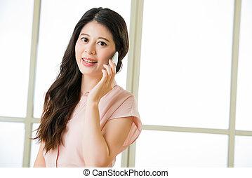 Beautiful young Asian woman using smart phone talking