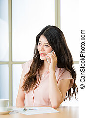 Beautiful young Asian woman using smart phone talking