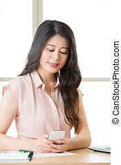 Beautiful young Asian woman using smart phone text messaging