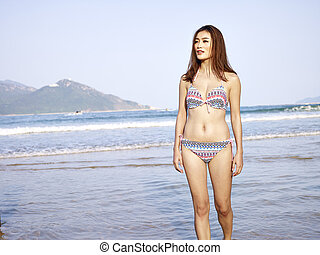 beautiful young asian woman walking on beach