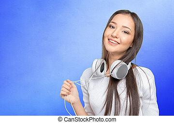 Beautiful young Asian woman wearing a set of headphones