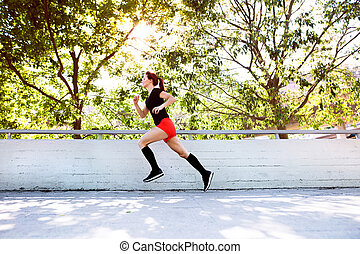 Beautiful young athlete running on a path in the city.