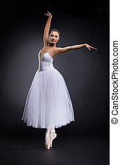 beautiful young ballet dancer on black. attractive ballerina standing tiptoe and looking