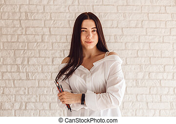 Beautiful young beautician woman holding set of make up brushes.