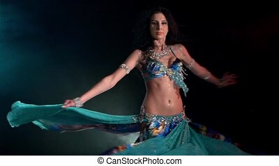 Beautiful young belly dancer dancing, slow motion, in smoke, on black