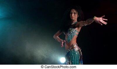 Beautiful young belly dancer finishing dancing, slow motion, in smoke, blue