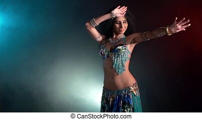 Beautiful young belly dancer go on dancing, slow motion, in smoke