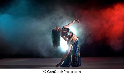 Beautiful young belly dancer in blue exotic costume continue dancing, modern, on black, red, smoke, slow motion