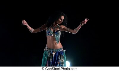 Beautiful young belly dancer in blue exotic costume continue dancing, modern, on black, smoke, slow motion