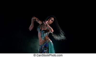 Beautiful young belly dancer in blue exotic costume finishing dancing, modern, on black, smoke, slow motion