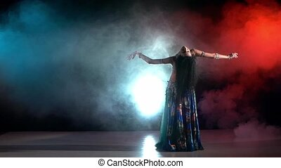 Beautiful young belly dancer in blue exotic costume go on dancing, on black, blue, red, smoke, slow motion