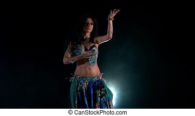 Beautiful young belly dancer in blue exotic costume, modern, on black, smoke, slow motion