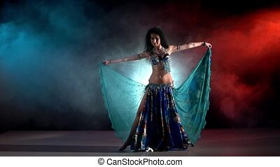 Beautiful young belly dancer in blue exotic costume starting dancing, modern, on black, red, blue, smoke, slow motion