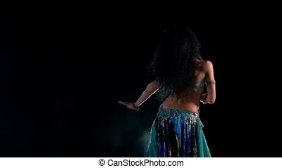 Beautiful young belly dancer in blue exotic costume starting dancing, modern, on black, smoke, slow motion