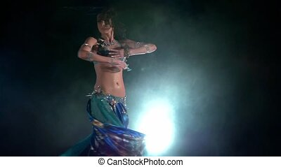 Beautiful young belly dancer in exotic costume, modern, on black, blue, smoke, slow motion