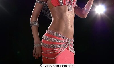 Beautiful young belly dancer in pink exotic costume continue dancing, modern, on black, smoke, slow motion, back light