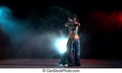 Beautiful young belly dancer, modern, on black, blue, red, smoke, slow motion