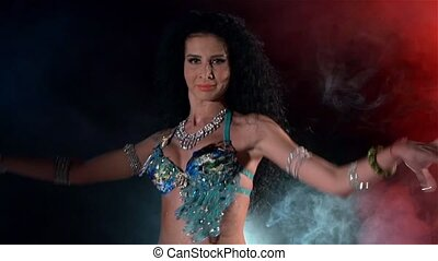 Beautiful young belly dancer, modern, on black, blue, red, smoke, slow motion, close up